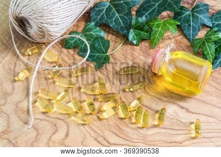 Transparent Gelatinous Capsules Of Fish Oil Were Scattered On The Wooden Background Near The Oil Bot