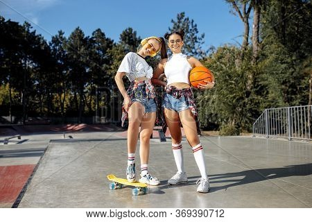Two Pretty Young Teenage Girls Posing With Happy Faces At The Skatepark. Skateboard And Basketball.