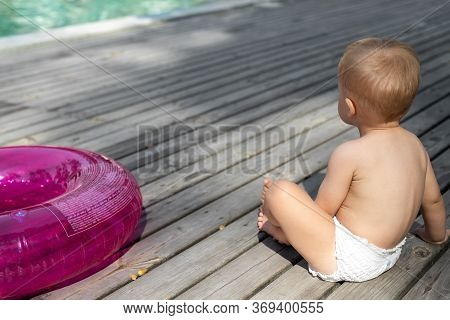 Cute Adorable Little Caucasian Blond Toddler Boy Kid In Diaper, Inflatable Ring Sitting Near Poolsid