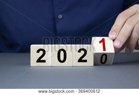 The Male Hand Holds A Wooden Cube Closeup With The Concept Of Changing The Year From 2020 To 2021 An