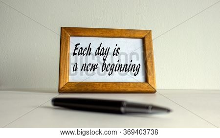 Wooden Picture Frame With Inscription 'each Day Is A New Beginning' On Beautiful White Fon. Pen On T