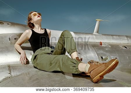 Beautiful girl pilot sits on the wing of a fighter airplane at the airfield.