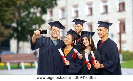 education, graduation and people concept - group of happy graduate students in mortar boards and bachelor gowns with diplomas taking selfie by smartphone over campus building background
