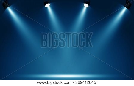Spotlights illuminate empty stage blue background.