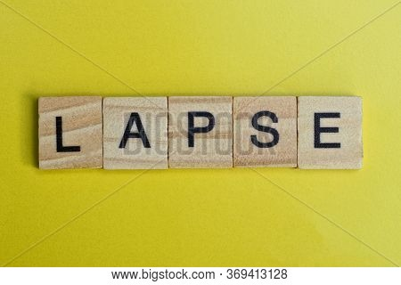 The Gray Word Lapse Of Gray Small Wooden Letters Lie On A Yellow Table