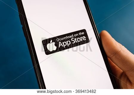 Smartphone In Hand With Download On The App Store Icon. High Quality Photo.