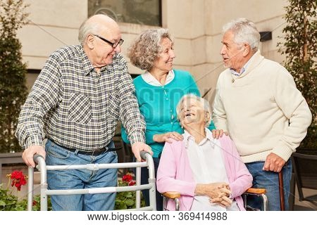 Happy group of seniors as friends in retirement home are having fun