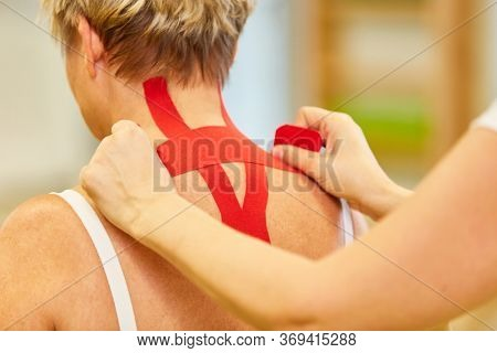 Woman gets a red kinesio tape in her neck for pain relief in cervical syndrome