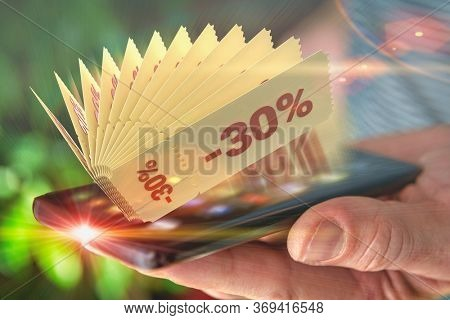 Hand holding smart phone with promo code coupons, concept of mobile phone application and shopping.
