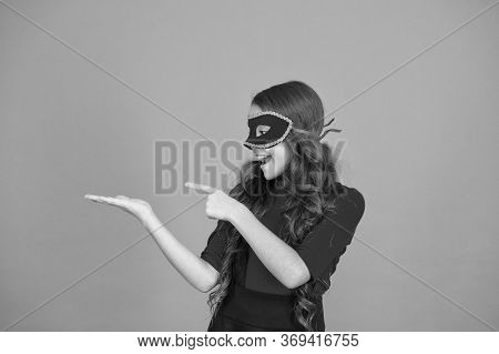 Focus On Advertising Campaign. Happy Girl In Carnival Mask Point Finger At Empty Hand. Product Adver