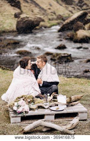 Destination Iceland Wedding, Near Kvernufoss Waterfall. A Wedding Couple Sits On The Banks Of A Moun