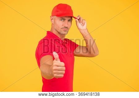 Try The Best Product. Serious Guy In Cap Give Thumbs Up Yellow Background. Approving And Promoting.