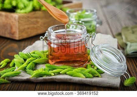 Jar Of Jam Or Honey From Fir Buds And Needles, Spoon With Flowing Syrup. Twigs Of Fir Tree On Wooden