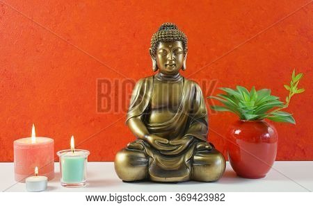 Zen Decor With Buddha Statue Against An Orange Textured Wall.
