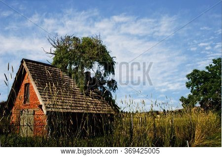 Old Brick Shed On Farm Land In Sonoma County California Against Blue And Cloudy Sky.
