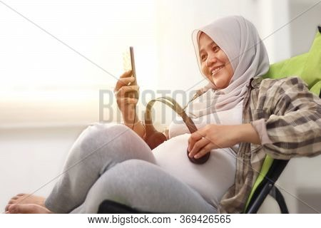 Beautiful Asian Muslim Pregnant Puts The Headphone On Her Tummy And Opens Quran Recitation Or Classi