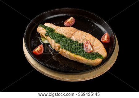 Salmon Steak With Pesto And Tomatoes In A Black Pan. Isolated On A Black Background.