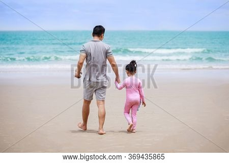 Happy Family. Happy Vacation Holiday. Father And Daughter Walking And Holding Hands On The Beach Tog