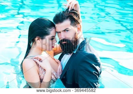 Couple With Suit In Swimming Pool. Beautiful Sensual Young Couple Embracing In Swimming Pool. Best S