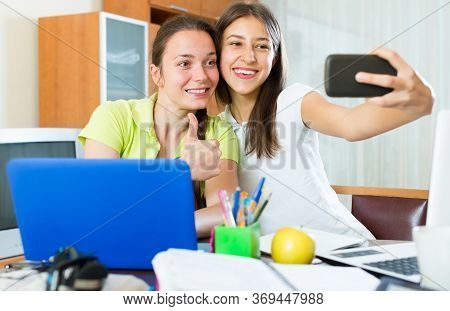 Happy Student Girls Sitting At The Table And Making Photo On Mobile Phone