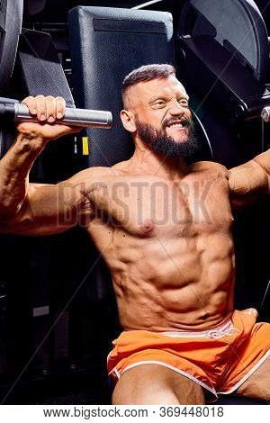 Handsome Male Bodybuilder In Gym. Big Strong Man During Training In The Gym. Guy With Big Muscles Wh
