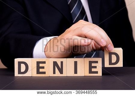Man Made Word Denied With Wooden Blocks. Business Concept.