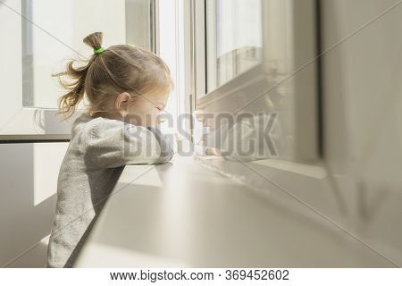 Little Girl Dreamily Looks Out The Window. The Sun Illuminates Her Face, Flare. The Child Is On Self