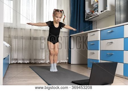 A Little Girl In A Black Gymnastics Leotard Is Doing Gymnastics At Home Online In Front Of A Laptop.
