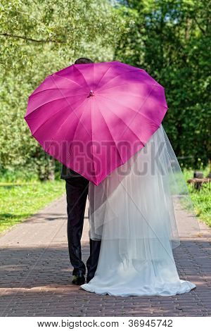 Newly-married couple in a summer garden under a pink umbrella in the form of heart