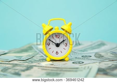Close-up Of Yellow Alarm Clock And Money On Blue Background. Business Finance And Money Concept. Sav