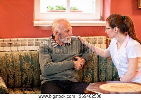 Caregiving Nurse Having A Conversation With Nursing Home Occupant