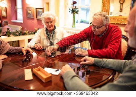 Group Of Senior People Having A Good Time While Playing A Game Of Dominos