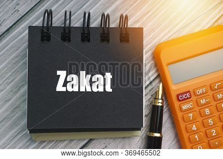 Zakat Or Islamic Tax  Text With Fountain Pen, Calculator And Notepad On Wooden Background. Zakat Is
