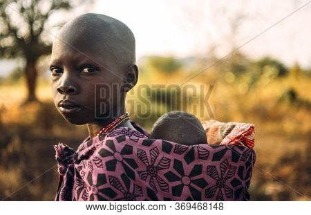 Boya Tribe, South Sudan - March 10, 2020: Girl In Traditional Colorful Garment Of Boya Tribe Carryin