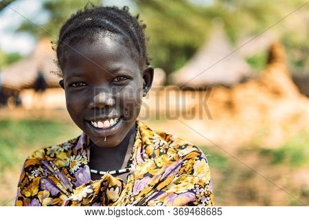 Boya Tribe, South Sudan - March 10, 2020: Girl In Traditional Colorful Outfit And Accessory Smiling