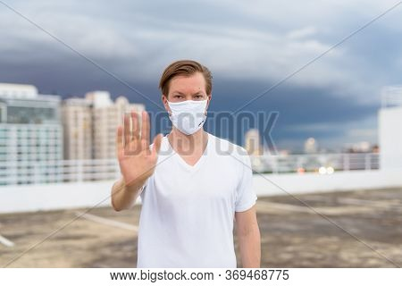 Young Man With Mask Showing Stop Gesture Against View Of The City During Stormy Weather Outdoors
