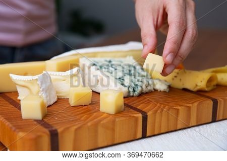 Hand Taking Piece Of Cheese From Wooden Board. Blue, Soft And Hard Cheeses. Brie, Camembert. Studio