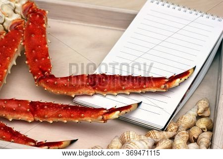 Legs Of A Cooked Crab And A Shells On A Wooden Tray . Clean Sheet For The Menu. Copy Space.