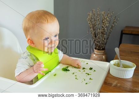 Happy Positive Baby Making Mess While Eating Broccoli Vegs And Soup. Little Child Wearing Plastic Bi