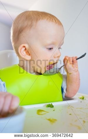 Focused Baby Training To Eat Spoon By Herself. Little Child Wearing Plastic Bib, Sitting In Highchai