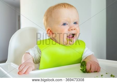 Adorable Baby Wearing Plastic Bib, Eating Broccoli In Highchair. Closeup Shot. First Solid Food Or C