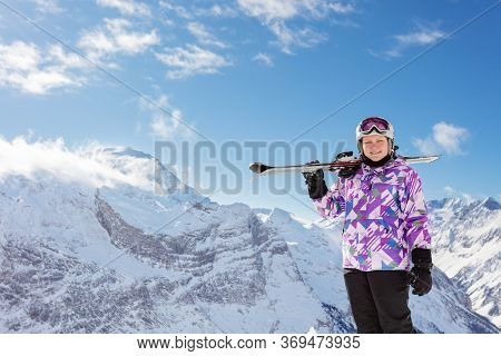 Teen Smiling Skier Girl Portrait Over High Mountain Summit In Helmet With Mask Smile And Hold Ski On