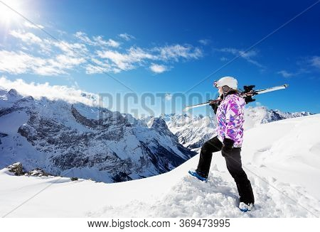 Profile View Of A Girl On Top Of The Mountain Skier Sportsman Stand And Hold Ski On The Shoulder Loo