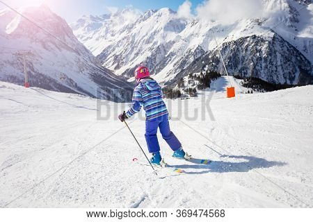 View From Behind On Young Girl Ski Fast Downhill On Winter Resort