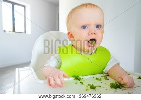 Annoyed Excited Baby Eating Broccoli Vegs, Looking Away With Open Mouth. Little Child Wearing Plasti