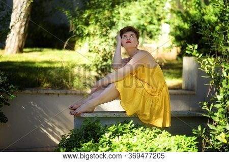Young Beautiful Caucasian Bored Displeased Girl With Short Haircut In Short Yellow Dress Sitting Out