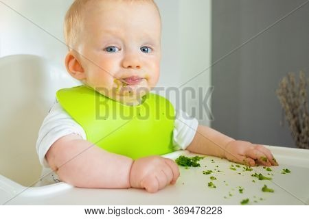Naughty Baby Trying To Eat Broccoli Vegs, Posing With Food Spots On Face, Making Messy On Tray. Litt