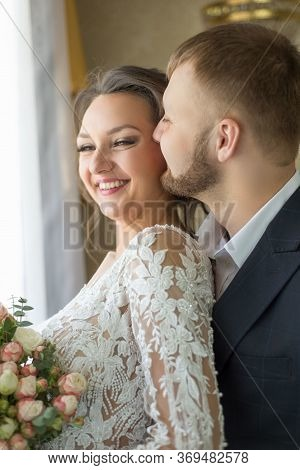Portrait Of A Happy Bride And Groom. The Groom Kisses The Bride. Smiling Young People Of Twenty-five