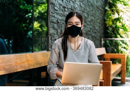 Asian Woman Wearing A Face Mask Outside While Sitting On Laptop. Dont Forget To Wear A Mask And Face
