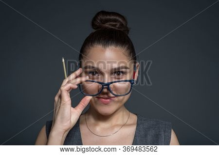 Portrait Of A Business Brunette Girl, Wearing Glasses, Holding A Pencil In Her Hand, Looking At The